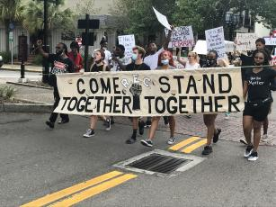 Participants in a march in Fernandina Beach hold up a sign that says Come Together - Stand Together.  Julia Roberts/News-Leader