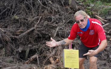 "SUBMITTED photos Flora Parke resident Alan ""Hupp"" Huppmann points to a stop work order issued by the county after a crew began clearing land near his home. Huppmann was just one of the neighbors alarmed by the activity. SUBMITTED"
