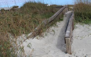 While the ADA ramp and Mobi-Mat that provide access to the beach at Main Beach are in good shape, allowing those in wheelchairs and with limited mobility to get out on the beach, the ADA ramp at Seaside Park has been overtaken by the dune. JULIA ROBERTS/NEWS-LEADER