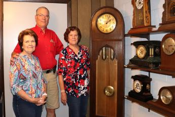 Raymond Fachko joins mother Patricia Fachko and aunt Kay Stokes as they stand near a collection of clocks Cliff Brandies owned. He and wife Lucille opened Brandies Home and Farm Supply in 1945, now known as Brandies Ace Hardware.