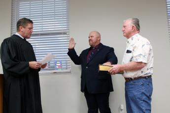 Newly elected Nassau County Commissioner Klynt Farmer takes the oath of office, administered by Circuit Judge Steve Fahlgren Oct. 20. Dad Kenny Farmer proudly holds the Masonic Bible for his son.