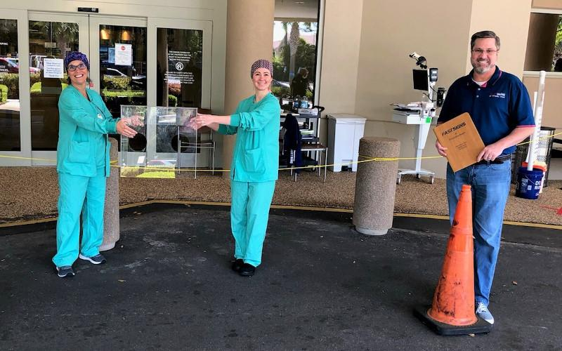 Eric Webb, franchise owner of FASTSIGNS in Fernandina Beach, and nurses at Baptist Medical Center Nassau observe social distancing while delivering intubation boxes at the hospital. SUBMITTED