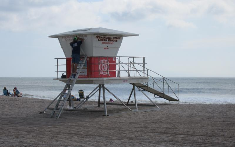 Personnel with Design It Wraps & Graphics in Fernandina Beach placed graphics on a new lifeguard tower at Main Beach. The tower, and another at Seaside Park, were installed Thursday. They were purchased from the National Park Service.  Julia Roberts/News-Leader