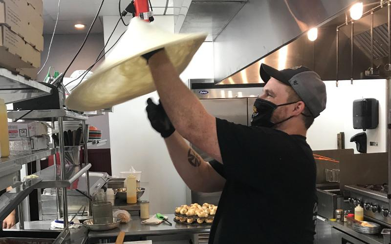 "Josh Sheppard has worked for Coastal Pizza for just under four years, coming with the company from Yulee to their new Amelia Island location. Twirling pizza dough into the air, he said he has fun at work, adding, ""I love what I do."" JULIA ROBERTS/NEWS-LEADER"