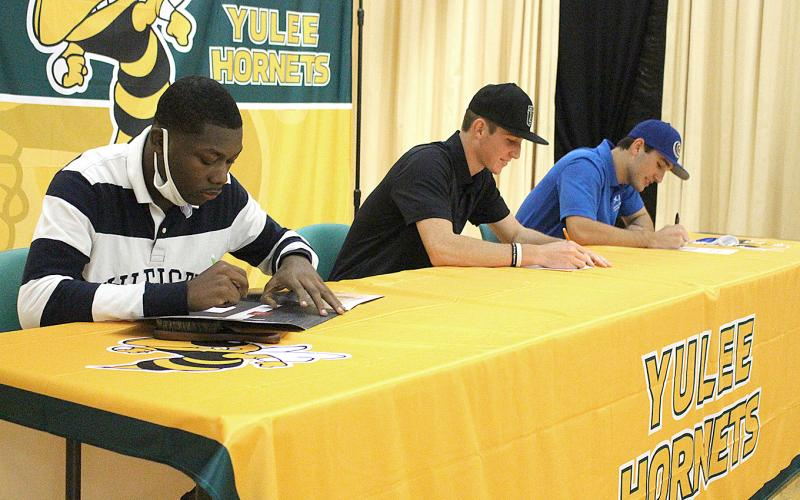 Left, D.J. Littlejohn, Ian Cochran and Josh Green, from left, signed national letters of intent Wednesday at Yulee High School.