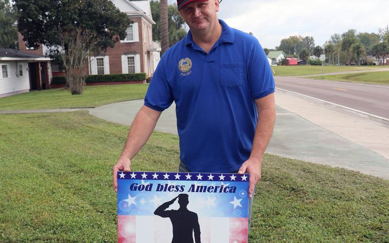 AMVETS of Nassau County Post 2007 Commander Randy Zakrzewski places a new patriotic sign in the ground. The signs are available for purchase to raise funds for AMVETS, a non-profit that assists area veterans.